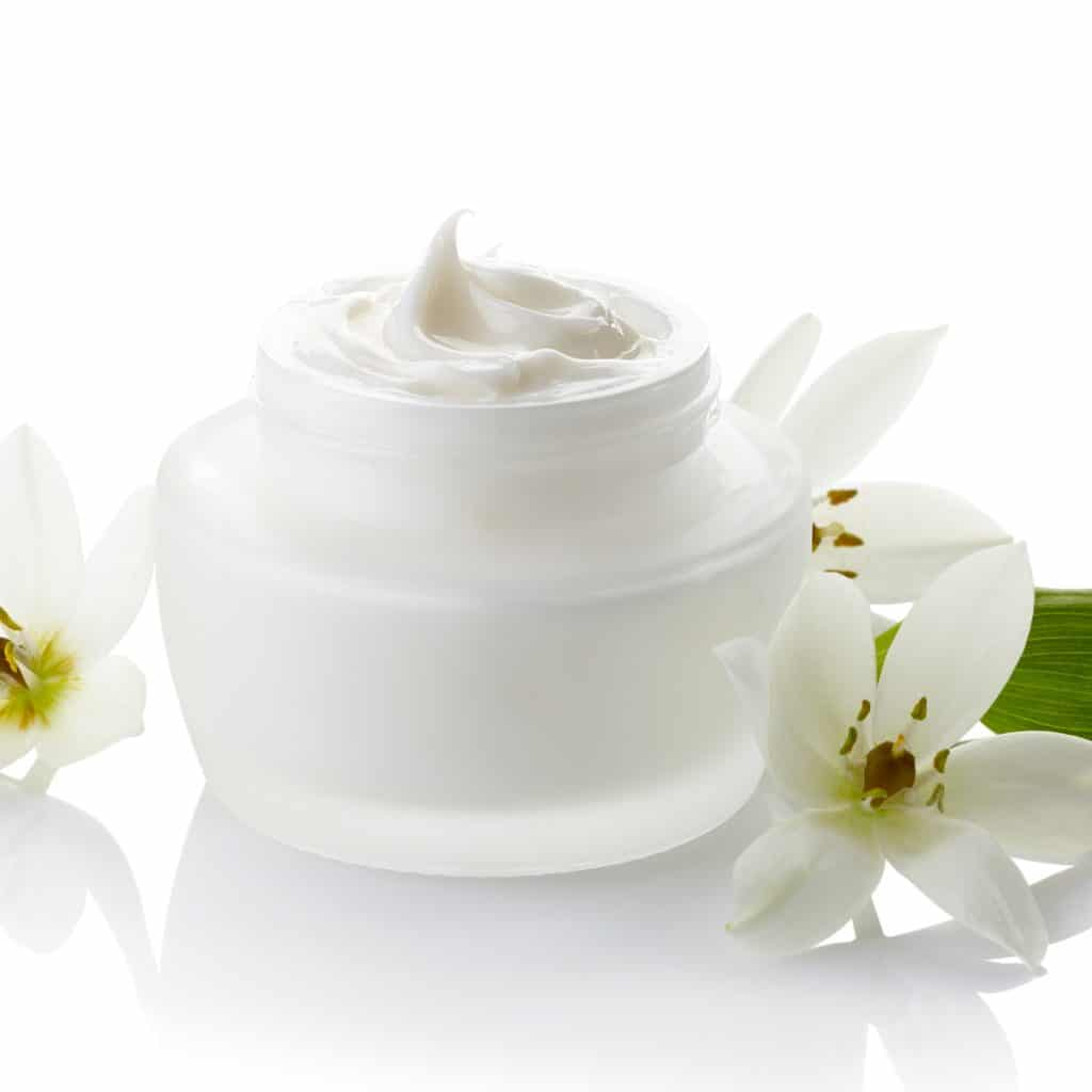 White jar of cosmetic cream and flowers isolated on white background