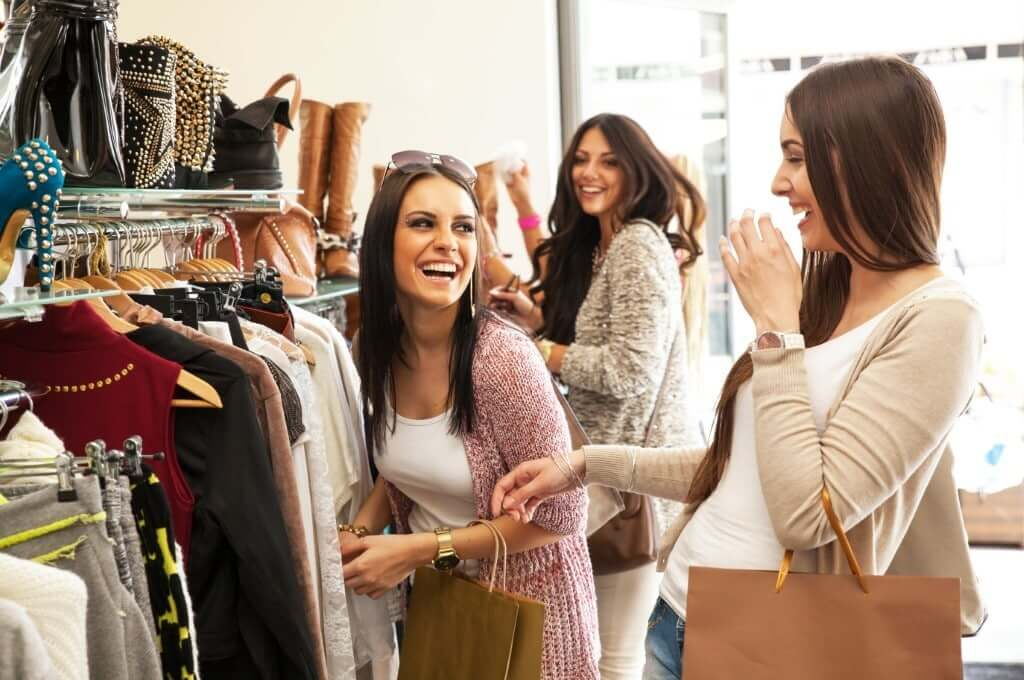 girls shopping laughing fashion store
