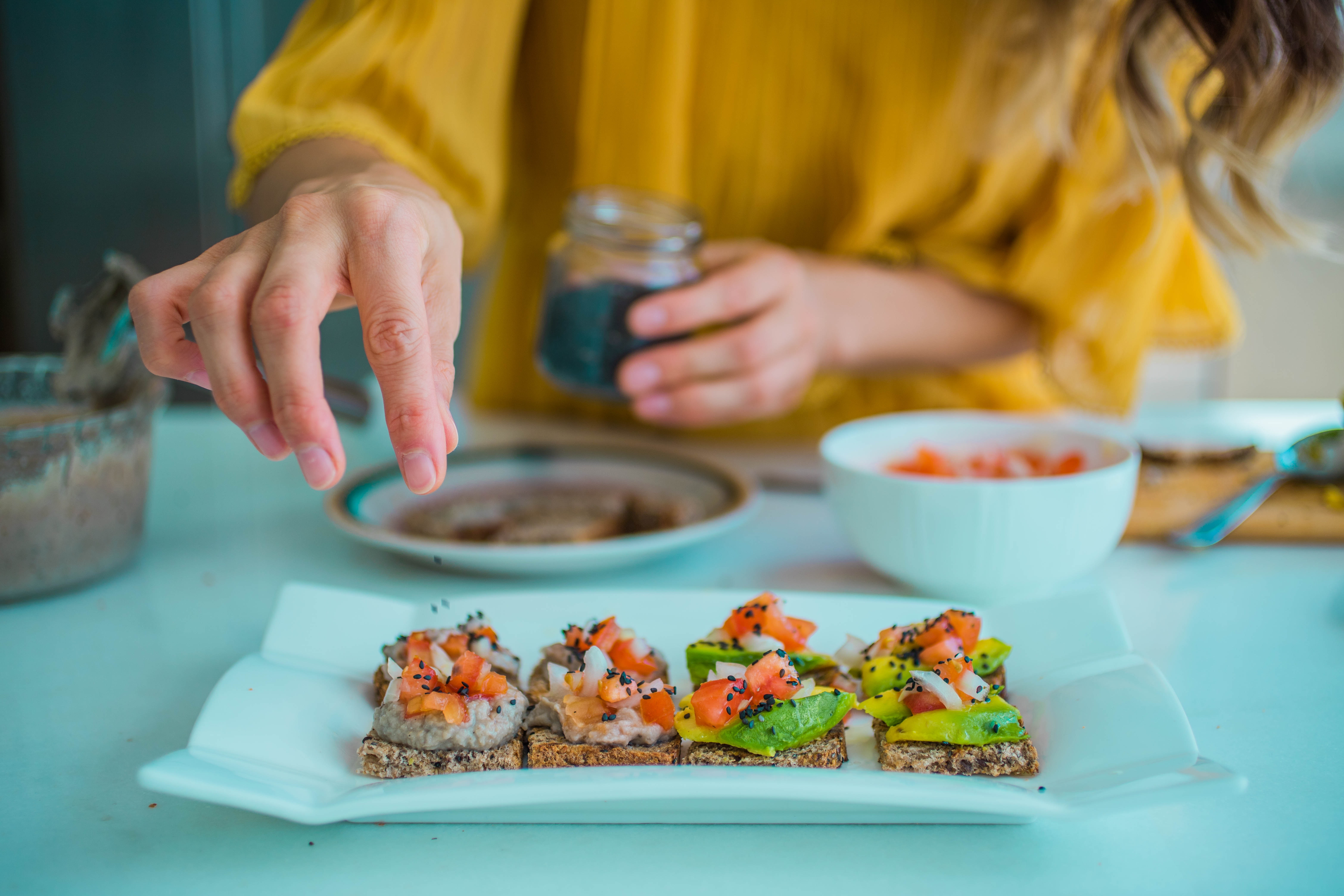 female hands arranging a plate with toasts with rice and avocado