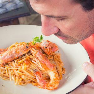 Men smelling plate of spaghetti with langostino