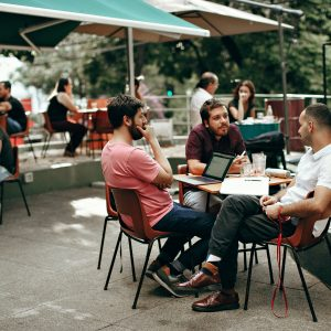 Three young men meeting outdoors at a coffee shop